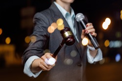 The auctioneer conducts the auction with a microphone on blurred background.