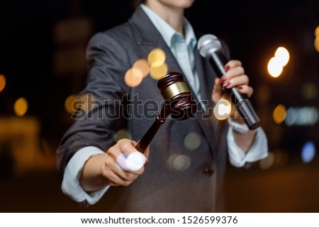 The auctioneer conducts the auction with a microphone on blurred background. ストックフォト ©