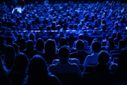 The audience in the cinema, the view from the back. Group of people at the business conference, back view, blue tones