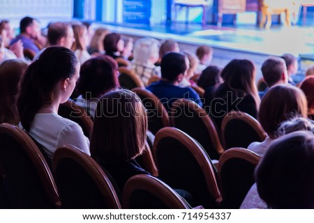 The audience in the theater watching a play. The audience in the hall: adults and children. #714954337