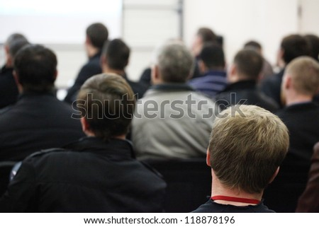 The audience listens to the acting in a conference hall.