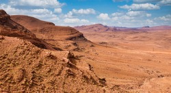 The austere beauty of the desolate Jbel Saghro mountain range, located in southern Morocco. A road is visible cut into the side of the rock on the left of the photo.