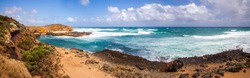 The Australian rocky coast is about 12 apostles. Strong winds drive ocean waves to the shore cliffs. A wide panorama. Sand dunes and cliffs. Blue sky with clouds on the horizon.
