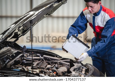 Photo of  The auto mechanic is about to change a new battery for the customers who come to use the battery replacement service at the shop.
