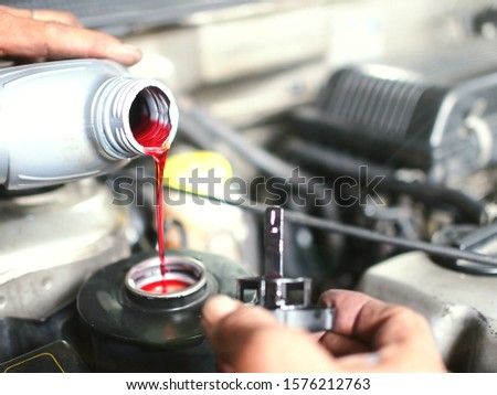 The auto mechanic is refilling additional brake fluid after the inspection and repair of the damaged parts. Сток-фото ©