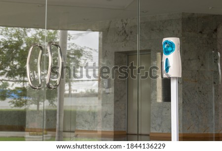 The automatic alcohol sprayer is in front of the entrance just before the entrance to the office. Stock photo ©
