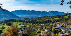 The autumn view over a small village to the Valley of Rhine and the Swiss mountains. the colorful trees and the yellow-green meadows makes a happy exhilarating impression. Feldkirch, Vorarlberg