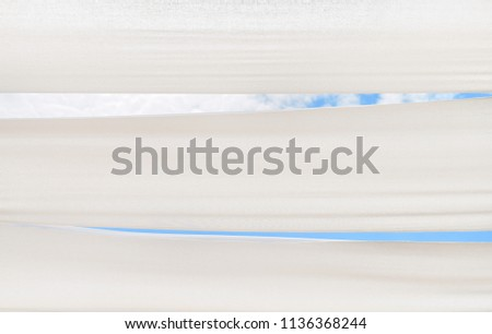 The awning over blue sky. Sky and clouds view from underneath between white canvas roof.  Copy space. Place for text. #1136368244