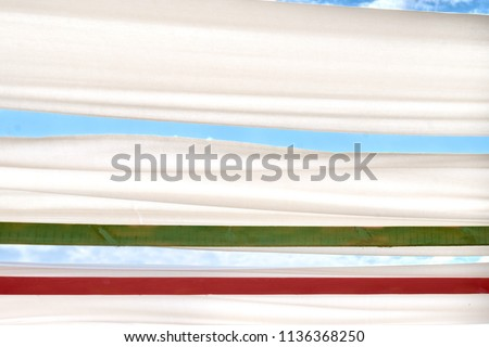 The awning over blue sky. Sky and clouds view from underneath between white canvas roof.  Copy space. Place for text. #1136368250