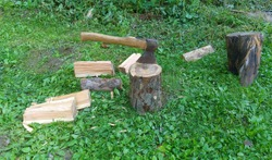 The axe is stuck in the deck against a background of green grass and chopped wood