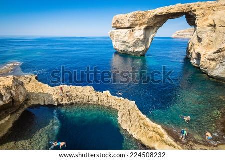 The Azure Window in Gozo island - Mediterranean nature wonder in beautiful Malta - Unrecognizable touristic scuba divers - World famous rock formation landmark collapsed after sea storm Stock fotó ©