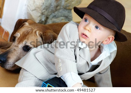 The baby boy and his brown hat and dog