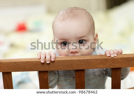 The baby boy biting a wooden cot at home