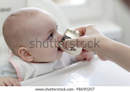 The baby boy drinking water from silver cup at home