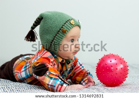 2da414e28 The baby boy is playing with a red little ball plaid shirt, green hat #
