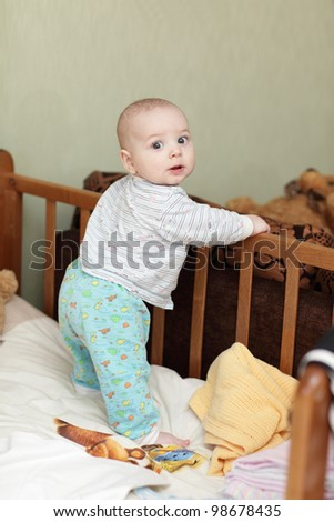 The baby boy standing in a cot at home