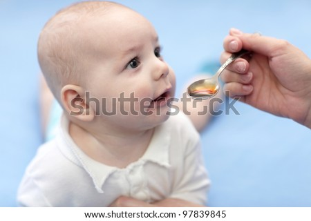 The baby boy taking spoon of iron medicine