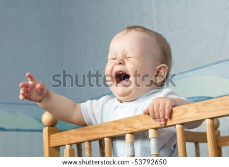 The baby cries and calls mum from a bed - stock photo