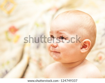 The baby cries and calls mum sitting at floor