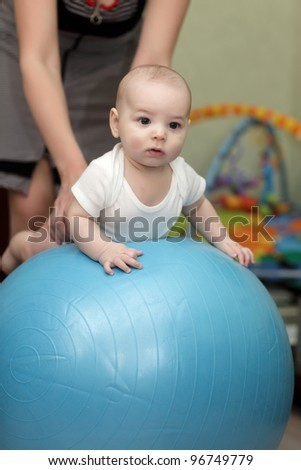 The baby exercises on a gymnastic ball at home