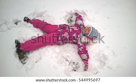 The baby girl is lying in the snow, happiness