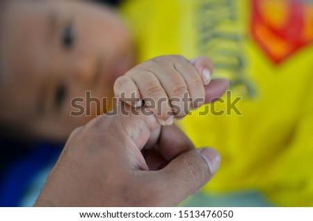 the baby holds his father's fingers tightly