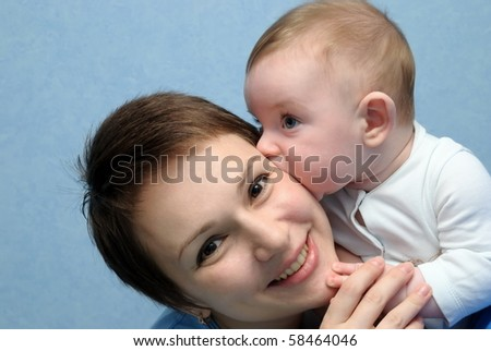 The baby kisses mum. A dark blue background