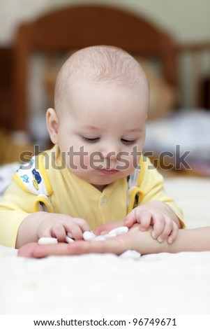 The baby takes pebbles from mother's hand