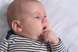 the baby who puts his hand in his mouth to suck his finger