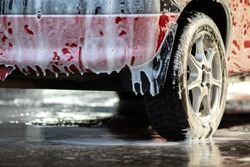 The back of a red passenger car at a car wash covered with foam. Close-up with a blurred background.