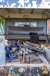 The back of an old dilapidated car filled with chairs and junk left in a yard