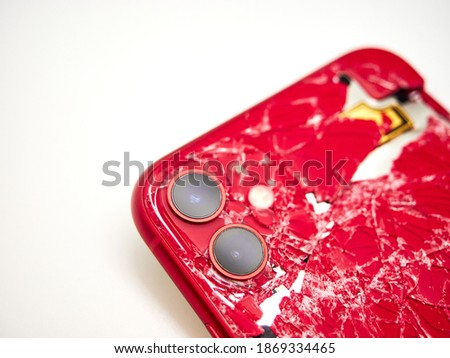 The back of modern red smartphone with a broken glass and a damaged curved body close-up isolated on white background Photo stock ©