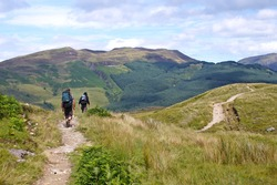 The back of some hikers along The West Highland Way through beautiful nature