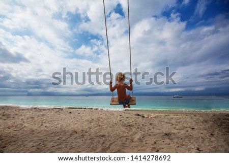 The back of the boys Swings are playing on the beach #1414278692