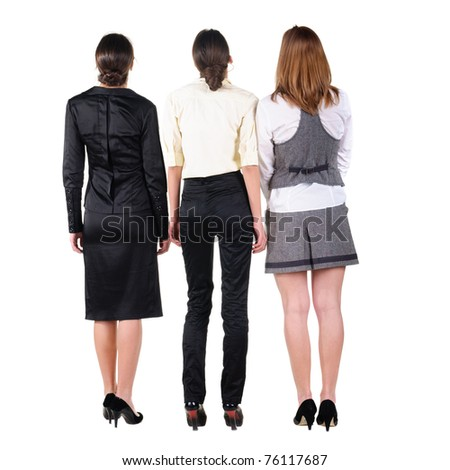 The back of three beautiful young bussines woman looking at wall. Rear view. Isolated over white.