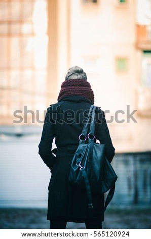 The back of young woman with lather bag in urban setting - Shutterstock ID 565120924