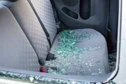 The back seat of a vandalized car with broken smashed glass covering the seat.  The car was broken into and stolen.