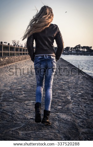 The back view of a girl walking down the village street in the wind, autumn
