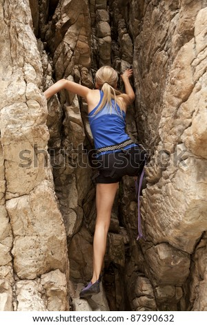 The back view of a woman rock climbing up a mountain, with ropes.