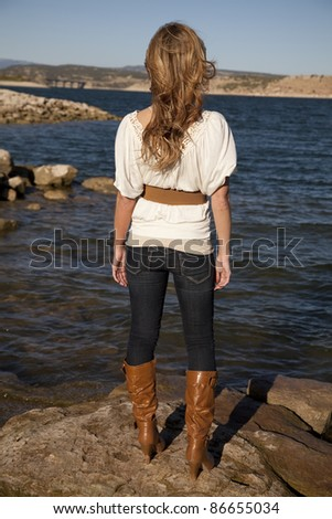 The back view of a woman standing on rocks looking out over the water.