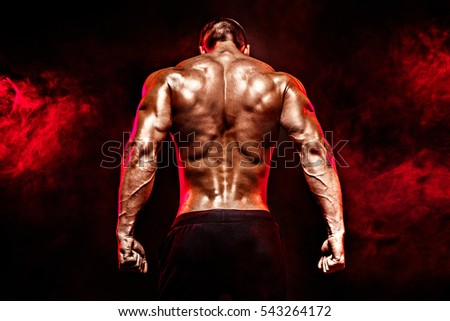 The back view of torso of attractive male body builder on dark smoky background. #543264172