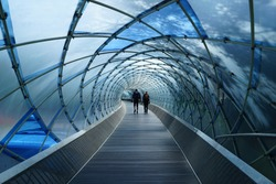 The back view of two people walking away together in blue translucent tunnel at anyang park, south korea