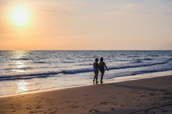 The back view of two women wearing bikinis walking on the beach vacations travel holiday, Beautiful sunset background.