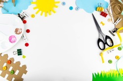 The background is a view from above on a white table with children's creativity. On the table of colored paper the sun, clouds, grass, fence, palette, scissors, colored buttons