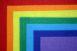 The background is made of felt of rainbow colors. Top view. Space for text.