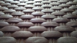 The background of a crafted chair woven in bright dark lighting