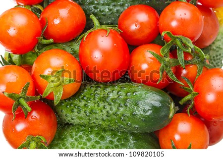 The background of red cherry tomatoes and green cucumber