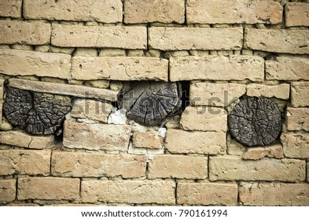 The background picture of the old brick and log wall, the house's wall in Nepal