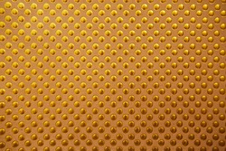 The background texture of a gold foil sheet wrapping paper with circles is brilliant for a Wallpaper decoration item or packaging.