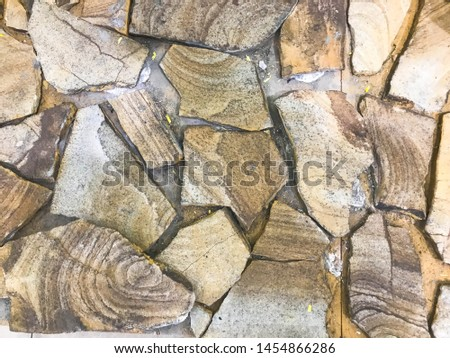 The background, the texture of large fragments of large carved brown sharp stones, cobblestones with cracks similar to the cut of the tree. #1454866286